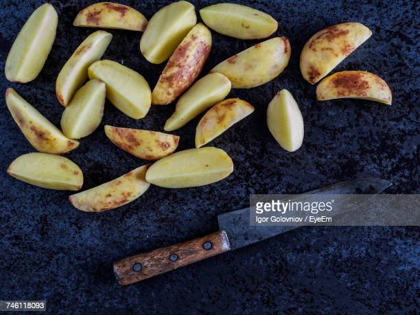 High Angle View Of Potato Slices And Knife On Kitchen Counter