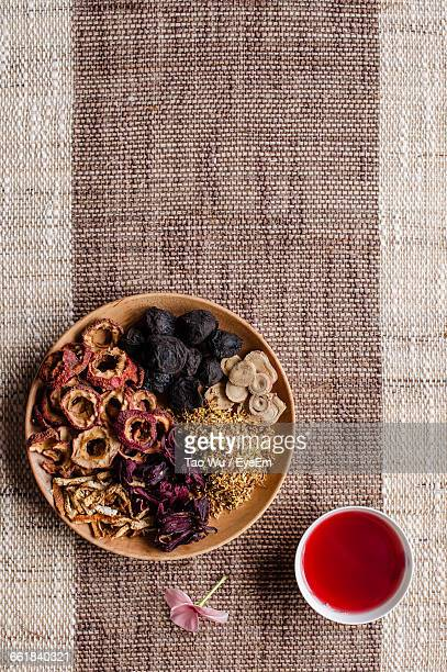 High Angle View Of Potpourri With Bowl Of Aromatic Oil On Mat