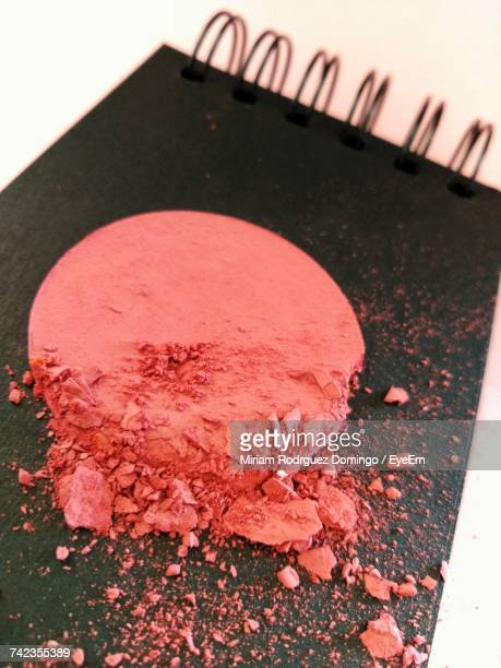High Angle View Of Powder Compact On Note Pad At Table