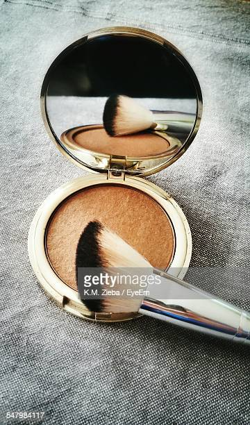 High Angle View Of Powder Compact With Make-Up Brush