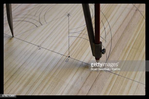 High Angle View Of Protractor With Drawings On Wood