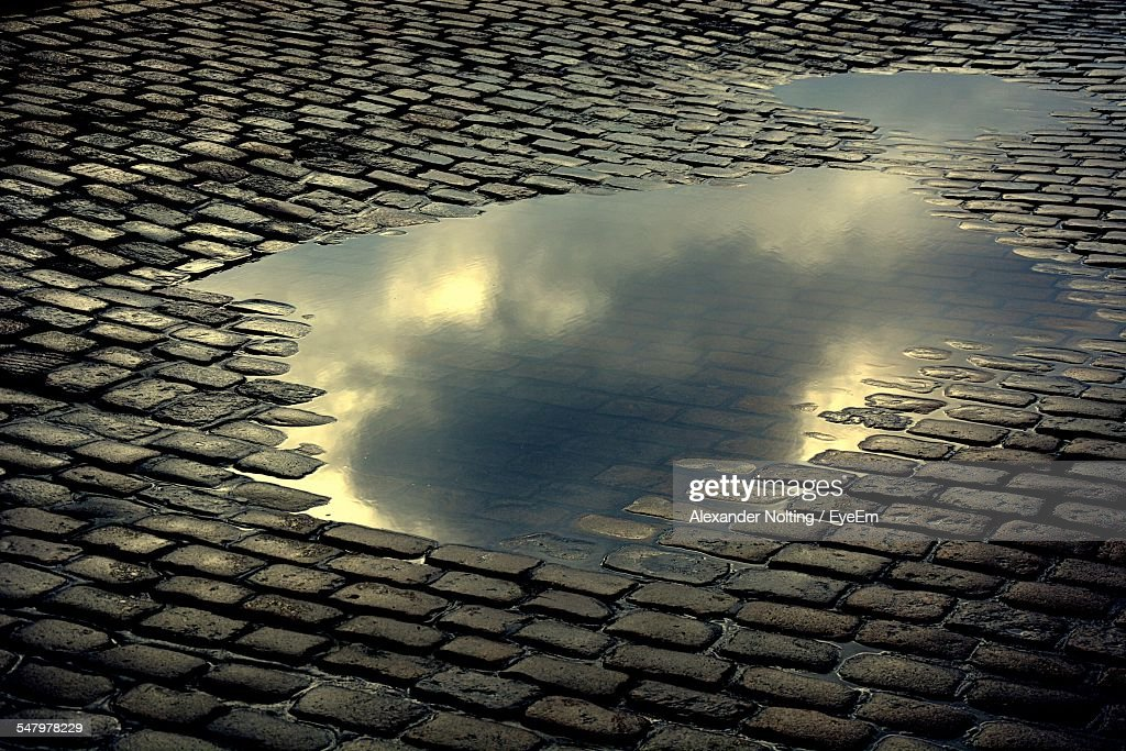 High Angle View Of Puddle On Footpath
