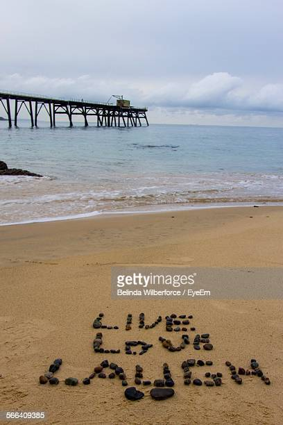 High Angle View Of Quote On Sand At Beach Against Pier