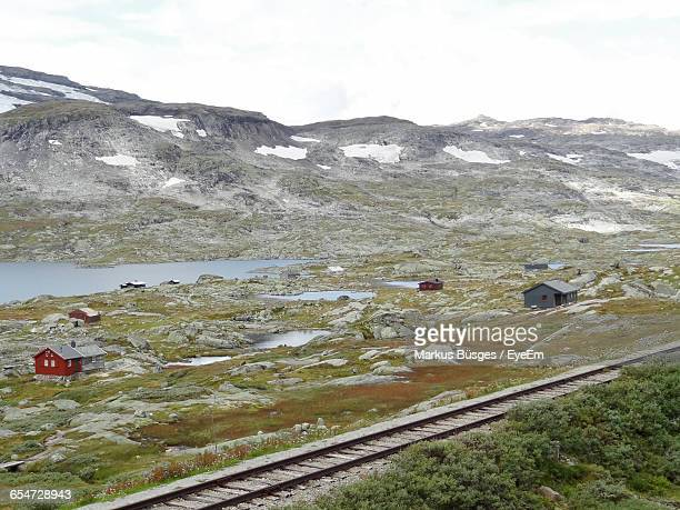 High Angle View Of Railroad Track By Lake And Mountains