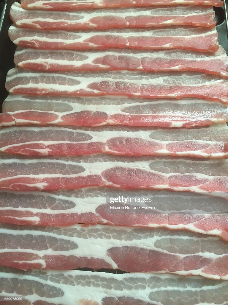 High Angle View Of Raw Bacons In Row On Table