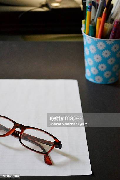 High Angle View Of Reading Glasses On Paper With Pen Holder