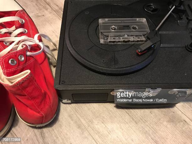 High Angle View Of Record On Briefcase With Canvas Shoes On Wooden Table