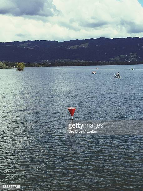 High Angle View Of Red Cone In Sea Against Cloudy Sky