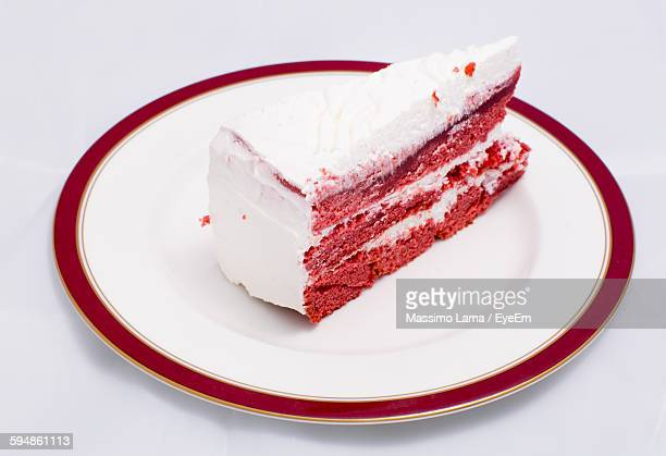 High Angle View Of Red Velvet Cake Served In Plate Against White Background