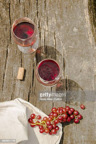 High Angle View Of Red Wine In Wineglass On Wooden Table