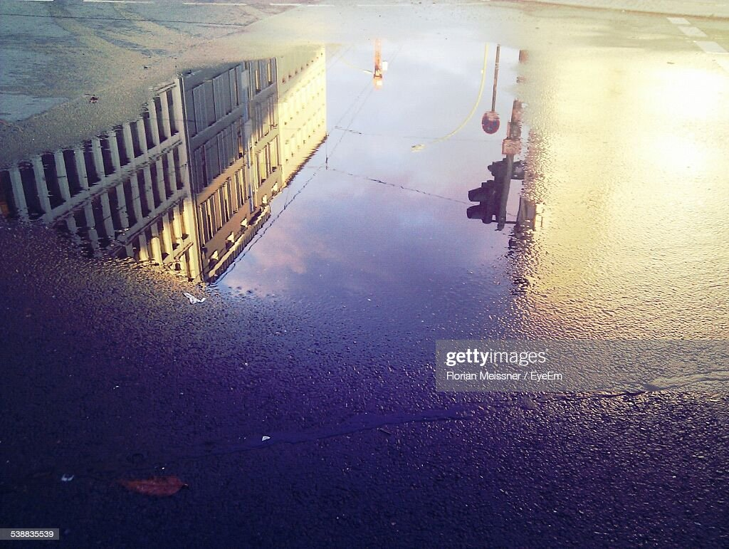 High Angle View Of Reflection Of Building On Puddle At Street