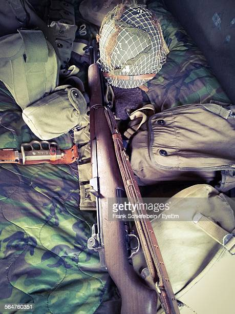 High Angle View Of Rifle, Helmet And Bags On Bed