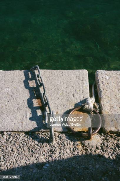 High Angle View Of Ring Bollard And Metal Chain On Pier Over Sea