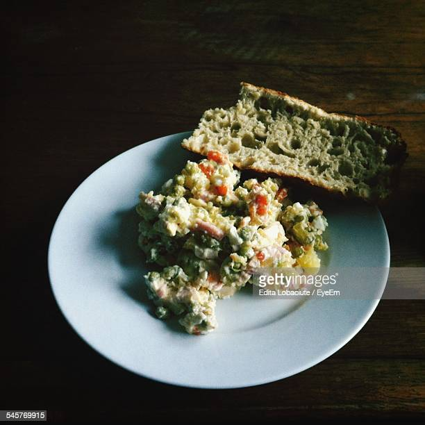 High Angle View Of Russian Salad With Bread On White Plate