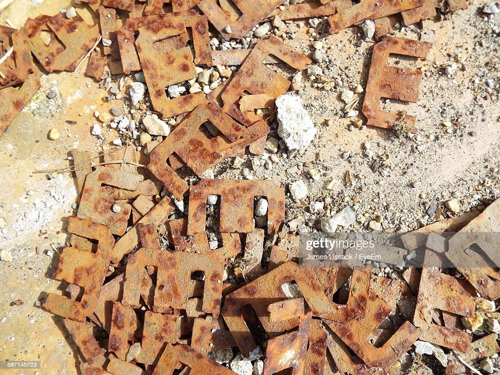 High Angle View Of Rusty Abandoned Metallic Letter E On Field