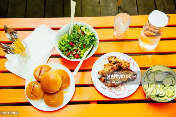 High angle view of salad, meat, cucumbers and salad on table