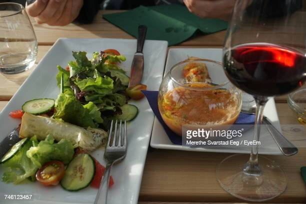 High Angle View Of Salad With Gravy And Red Wine On Table