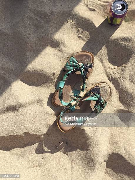 High Angle View Of Sandal And Drink Can On Sand At Beach