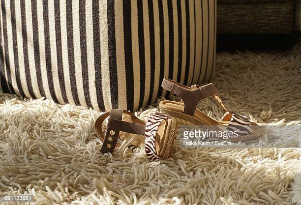 High Angle View Of Sandal By Furniture On Rug At Home
