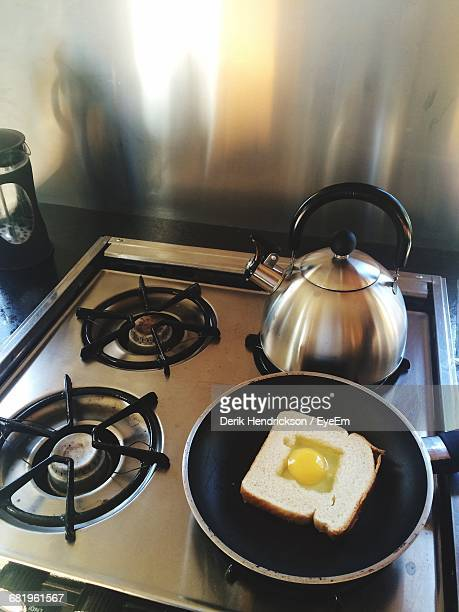 High Angle View Of Sandwich And Tea Kettle On Gas Stove Burners