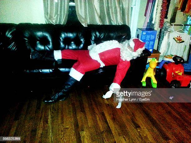 High Angle View Of Santa Clause Sleeping On Sofa At Home