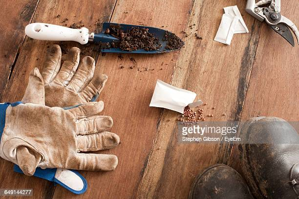High Angle View Of Seed Packet With Gardening Equipment And Boots On Table