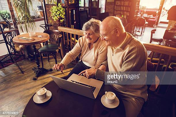 High angle view of senior couple shopping online in cafe.