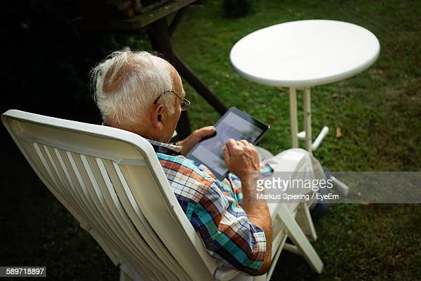 High Angle View Of Senior Man Using Digital Tablet While Sitting At Lawn