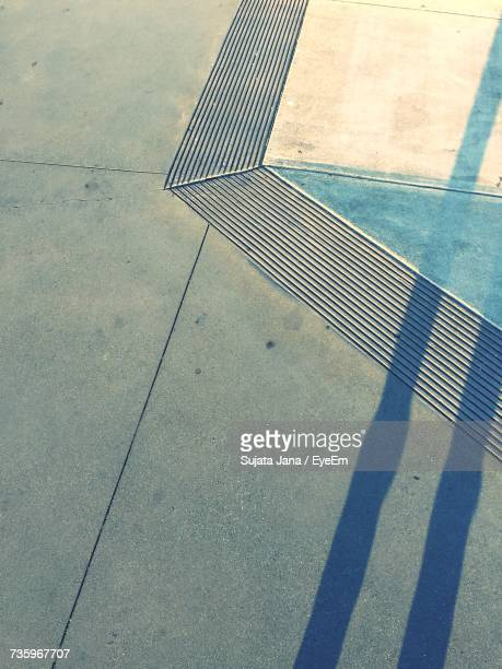 High Angle View Of Shadow Falling On Footpath