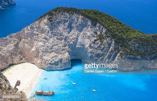 High Angle View Of Shipwreck On Beach In Front Of Rock Formation