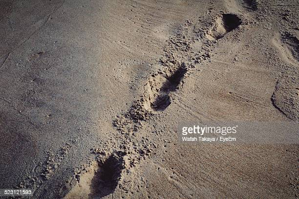 High Angle View Of Shoe Prints On Sand At Beach