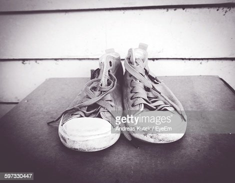High Angle View Of Shoes On Table Against Wall