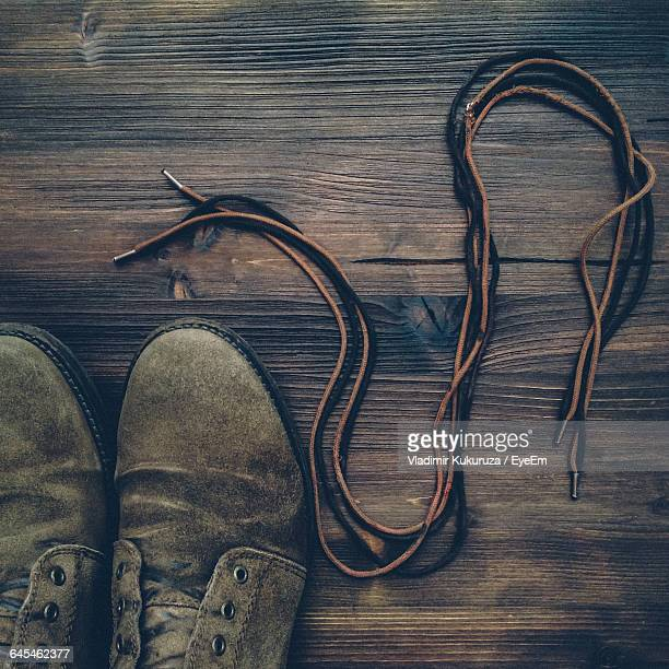 High Angle View Of Shoes With Lace On Floorboard
