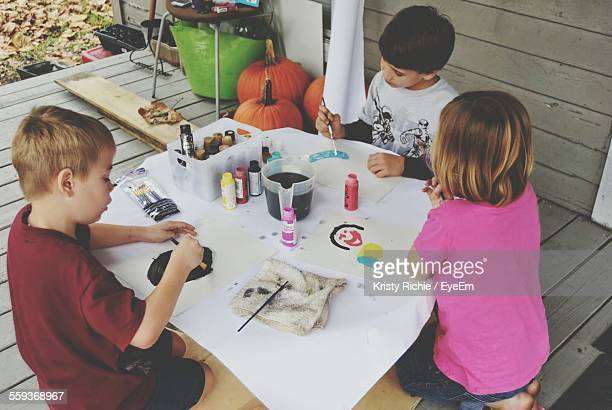 High Angle View Of Siblings Drawing On Papers At Table