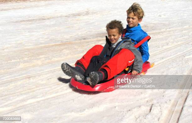High Angle View Of Siblings Enjoying Tobogganing On Sunny Day