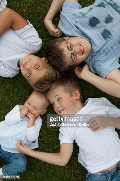 High Angle View Of Siblings Lying On Grass
