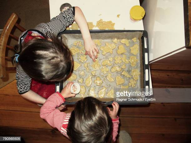 High Angle View Of Siblings Making Cookies At Table In House