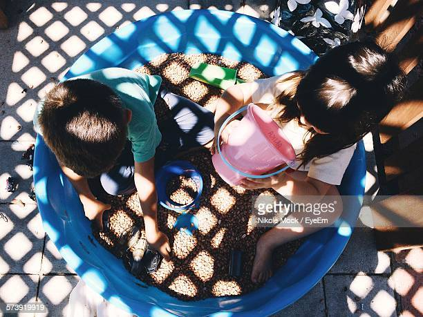 High Angle View Of Siblings Playing In Tub