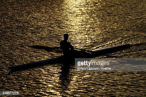 High Angle View Of Silhouette Man On Wooden Raft Sailing In Sea