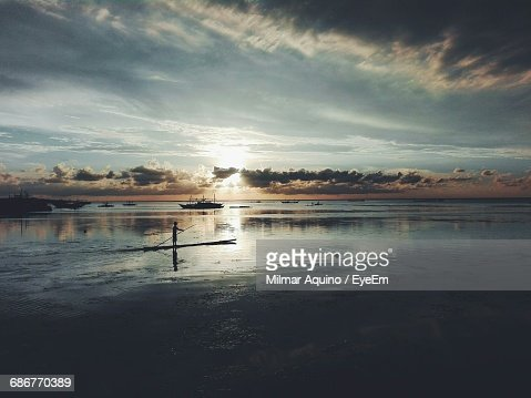 High Angle View Of Silhouette Man Sailing Wooden Raft On Sea