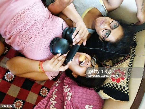 High Angle View Of Sisters Lying On Bed At Home