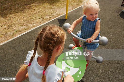 High angle view of sisters sitting on seesaw