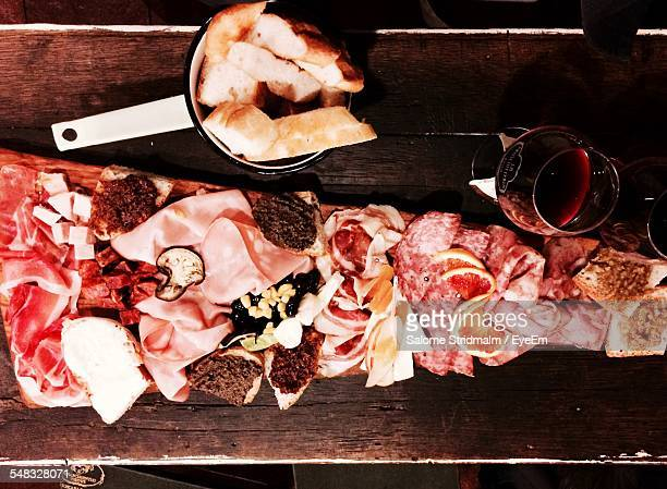 High Angle View Of Slice Hams And Breads On Chopping Board