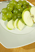 High angle view of sliced apple with grapes in a plate