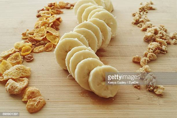 High Angle View Of Sliced Bananas And Breakfast Cereals On Wooden Table