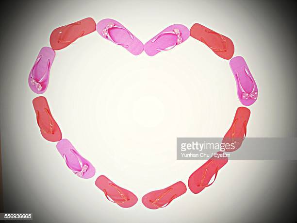High Angle View Of Slippers Forming Heart Shape Against White Background