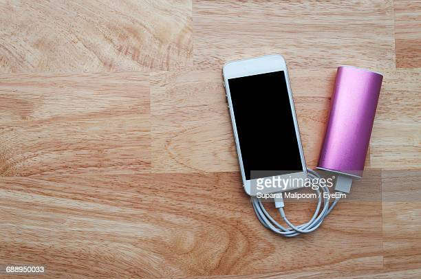 High Angle View Of Smart Phone With Battery Charger On Table