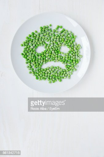 High Angle View Of Smiley Face Made Of Green Peas In Plate