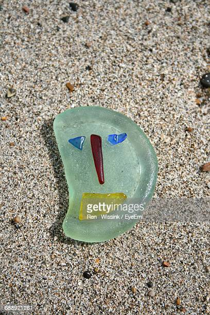 High Angle View Of Smiley Face On Glass At Beach