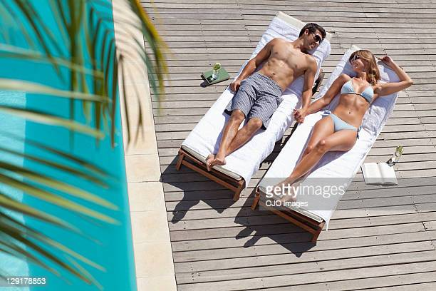 High angle view of smiling couple relaxing on deck chairs